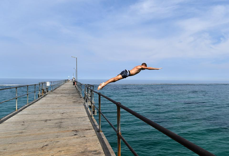 A swimmer jumps from the Port Noarlunga Jetty in Adelaide.