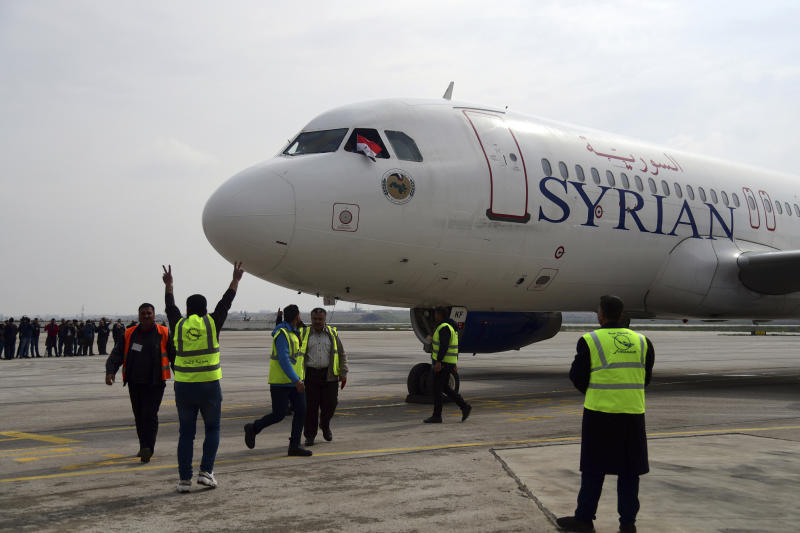 This photo released by the Syrian official news agency SANA, shows workers welcoming a Syrian commercial plane carrying Syrian officials and journalists after it landed at Aleppo Airport, Syria, Wednesday, Feb. 19, 2020. The Syrian commercial flight on Wednesday from Damascus, marked the resumption of internal flights between Syria's two largest cities for the first time since 2012. (SANA via AP)