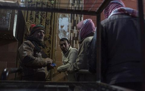 Men queue up to buy bread outside a bakery on te hotskirts of Qamishli - Credit: Sam Tarling
