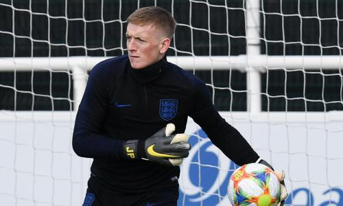 """<span>England goalkeeper Jordan Pickford during a training session at St George's Park ahead of their match against Montenegro. </span> <span>Photograph: Paul Ellis/AFP/Getty Images</span> <p>Gradski Stadion is one of Europe's less accommodating venues for international football. Only around 15,000 will cram into Montenegro's home ground to see if England can be overcome on Monday but they will make the noise of a crowd double the size.</p> <p>The stands at either end are concrete, compact and severe, hemmed close to the bylines in a manner reminiscent of Loftus Road. The home fans have a reputation for pushing the boundaries and England have found their limits tested in previous visits.</p> <p>Only Kyle Walker remains from the squad who travelled in 2013 and returned bruised by a <a href=""""https://www.theguardian.com/football/2013/mar/26/montenegro-england-world-cup-qualifier"""" rel=""""nofollow noopener"""" target=""""_blank"""" data-ylk=""""slk:late equaliser from Dejan Damjanovic"""" class=""""link rapid-noclick-resp"""">late equaliser from Dejan Damjanovic</a>. That was low-key fare compared with what passed 17 months previously on a night that brought Montenegro as close to success as they have been since being granted Uefa membership in January 2007.</p> <p>On a chaotic evening that had started serenely, England lost their way. Ashley Young and Darren Bent seemed to have put them in an impregnable position but then Elsad Zverotic pulled one back, Wayne Rooney lost his head and was sent off, and Andrija Delibasic sparked a pitch invasion by <a href=""""https://www.theguardian.com/football/2011/oct/07/montenegro-england-euro-2012"""" rel=""""nofollow noopener"""" target=""""_blank"""" data-ylk=""""slk:levelling in stoppage time"""" class=""""link rapid-noclick-resp"""">levelling in stoppage time</a>. The point took England to Euro 2012 anyway; it gave Montenegro a play-off spot, too, but they still await qualification for a major finals and will need to upset the odds again.</p> <p>""""Things that happen in the past are"""