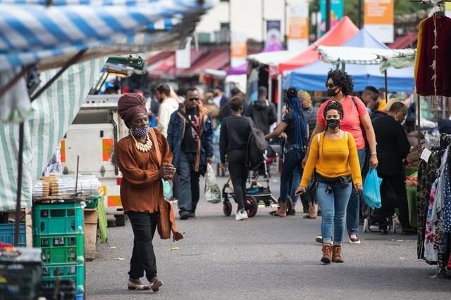 Shoppers wearing protective face masks at Ridley Road Market in Dalston, London (Dominic Lipinski/PA)