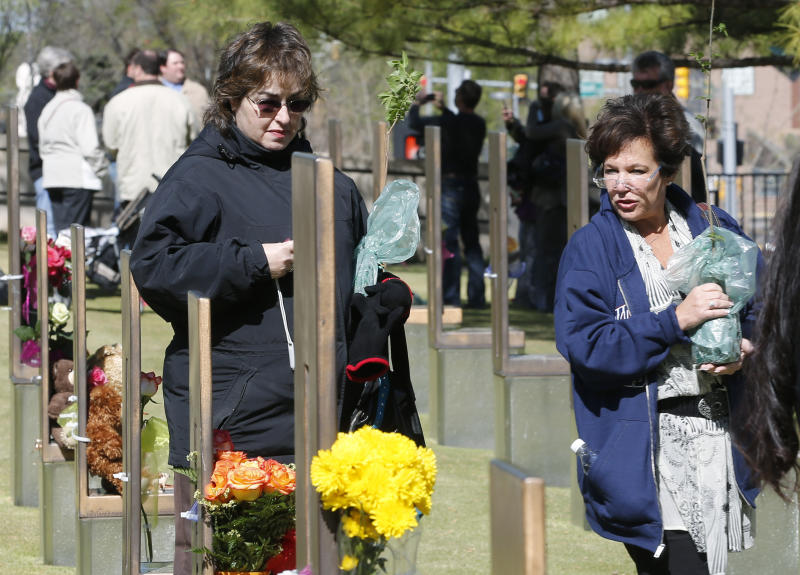 Lori Shulman, left, and Wendy Feinbert-Kotula, right,9-11 ambassadors, walk through the Field of Chairs at the Oklahoma City National Memorial in Oklahoma City, Friday, April 19, 2013, the 18th anniversary of the bombing. They are carrying cuttings of the Survivor Tree, which they will take back to their homes in New Jersey. Similar to previous years, 168 seconds of silence was observed at 9:02 a.m., when a truck bomb detonated outside the federal building. Survivors and family members recited the names of those killed in the attack. (AP Photo/Sue Ogrocki)