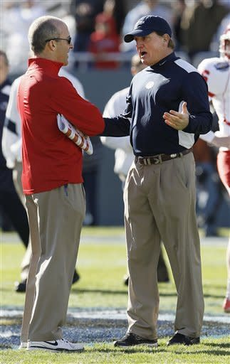 Houston head coach Tony Levine, left, and Penn State interim head coach Tom Bradley meet before the first half of the TicketCity Bowl NCAA college football game, Monday, Jan. 2, 2012, at the Cotton Bowl in Dallas. (AP Photo/Brandon Wade)