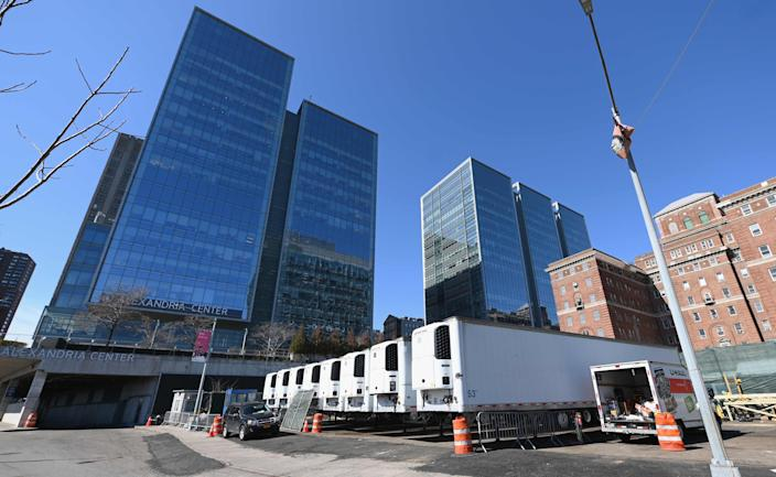 Refrigeration trucks are in place as workers build a makeshift morgue outside of Bellevue Hospital to handle an expected surge in coronavirus deaths.