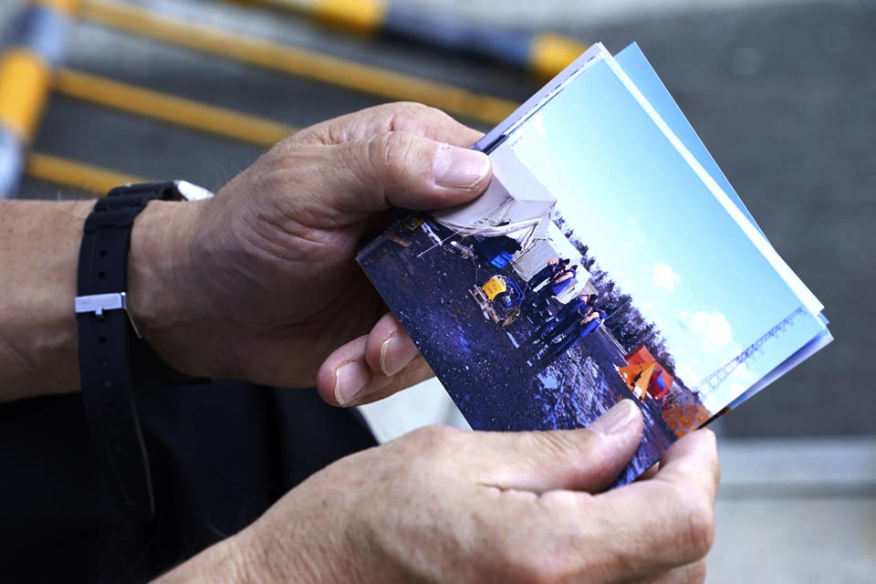 """Olympic volunteer Atsushi Muramatsu shows photos of Russian rescuers he took at Sekisui Heim Super Arena on March 18, 2011, when it was used as a morgue following a devastating March 2011 earthquake, during an interview with The Associated Press in Rifu, Japan, Thursday, July 29, 2021. The Tokyo Olympics was billed as the """"Recovery and Reconstruction Games,"""" with the torch relay starting in disaster-hit Fukushima and several events held in Fukushima and Miyagi. However, the coronavirus pandemic has disrupted opportunities to showcase the region's restoration to foreign spectators. (AP Photo/Chisato Tanaka)"""