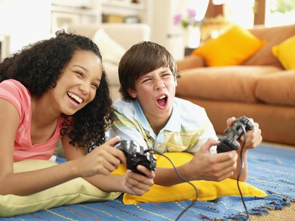 Two children react while playing a console game.