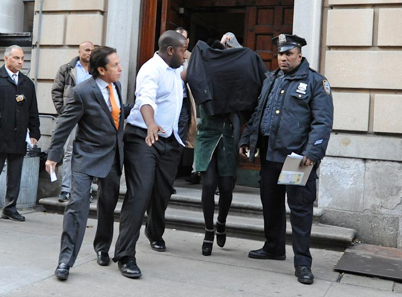 FILE - Lindsay Lohan, second from right, is escorted from the 10th Precinct police station, with her face shielded, in this Nov. 29, 2012 file photo taken in New York after being charged for allegedly striking a woman at a nightclub. Lohan is scheduled to appear in court Monday Jan. 7, 2013 to face assault charges in connection with the fight at a Manhattan nightclub. (AP Photo/ Louis Lanzano)