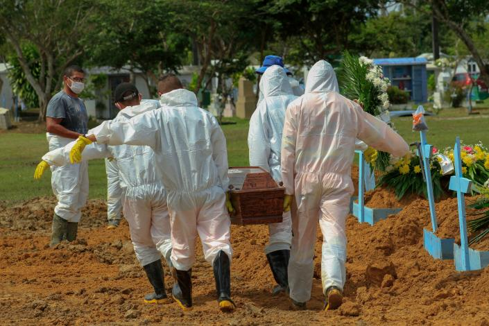 Gravediggers carry the coffin of a COVID-19 victim at the Nossa Senhora Aparecida cemetery in Manaus, Amazonas state, Brazil, on January 22, 2021, amid the novel coronavirus pandemic. (Marcio James/AFP via Getty Images)