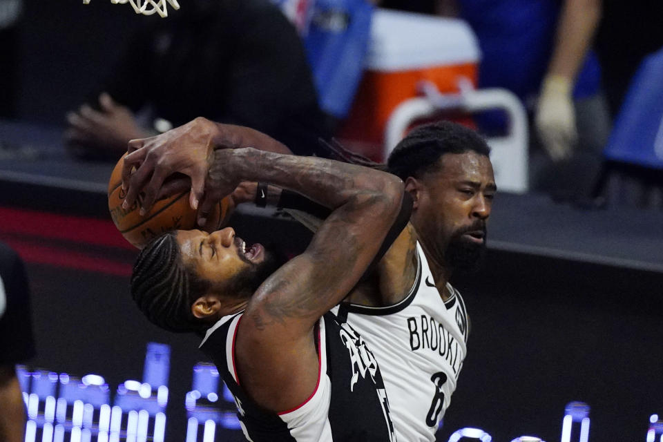 Los Angeles Clippers guard Paul George, left, is fouled by Brooklyn Nets center DeAndre Jordan during the second half of an NBA basketball game Sunday, Feb. 21, 2021, in Los Angeles. (AP Photo/Mark J. Terrill)