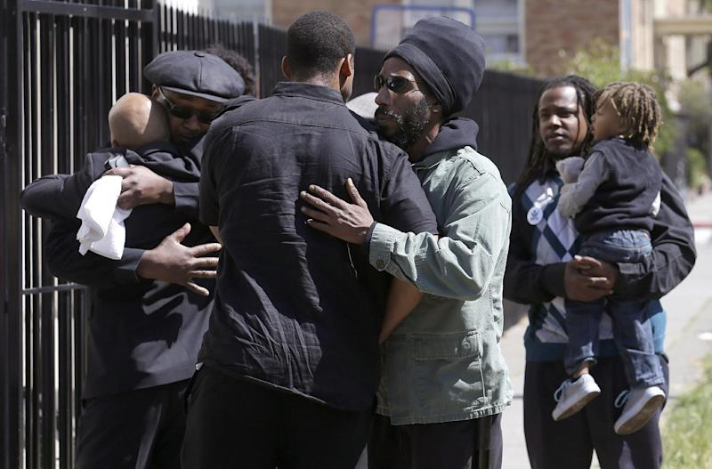 People attending a service for Malcolm Shabazz, the grandson of Malcolm X, hug as they arrive at the Islamic Center of Northern California in Oakland, Calif., Friday, May 17, 2013. Authorities say Shabazz was beaten to death last week in a dispute over a $1,200 bar bill in Mexico City. The 28-year-old grandson of the slain civil rights leader had a troubled life, from setting a blaze in his grandmother's apartment that resulted in the death of Malcolm X's widow, Betty Shabazz, to stints in juvenile hall and prison. (AP Photo/Jeff Chiu)