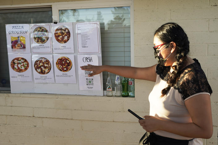 Ruby Salgado, points to the pizza menu posted outside her home at her family's makeshift pizza restaurant in Scottsdale, Ariz. on April 3, 2021. Beaten down by the pandemic, some laid-off or idle restaurant workers have pivoted to dishing out food from home. Salgado, 26, and her husband, Jose Hernandez, spend their weekends making pizzas in a backyard oven they built. Some nights, they churn out as many as 30 pies with toppings like fennel sausage, fresh mozzarella and carne asada. (AP Photo/Ross D. Franklin)