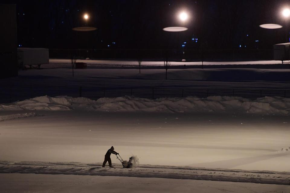 <p>A man begins to clear a parking lot in the late-night hours Wednesday in Wilkes Barre, Pennsylvania. </p>