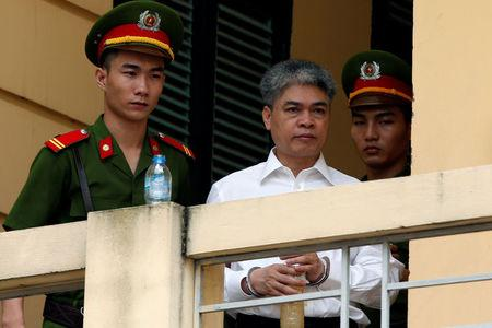 Former Petro Vietnam (PVN) chairman Nguyen Xuan Son (C) is escorted by police while he leaves the court after the verdict session in Hanoi, Vietnam September 29, 2017. REUTERS/Kham