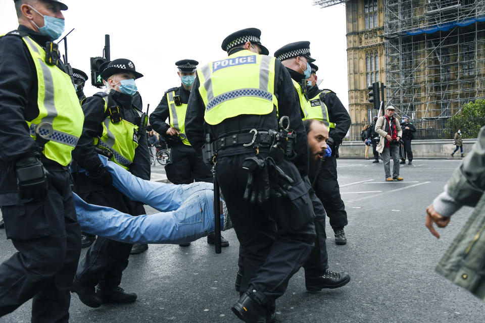 Police detain a man, during a coronavirus anti-lockdown protest on Westminster Bridge, in London, Saturday, Oct. 24, 2020. (AP Photo/Alberto Pezzali)