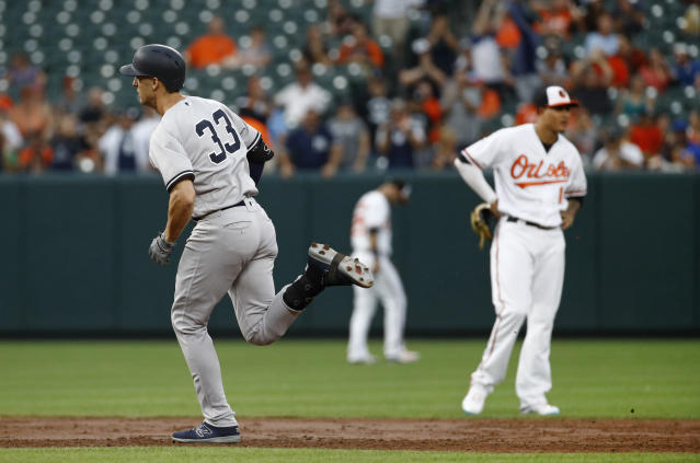 New York Yankees' Greg Bird, left, rounds the bases past Baltimore Orioles shortstop Manny Machado after hitting a grand slam during the third inning of a baseball game Wednesday, July 11, 2018, in Baltimore. (AP Photo/Patrick Semansky)