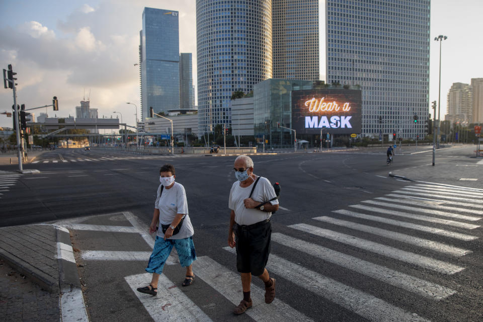 People wearing face masks cross a road next to a billboard calling people to wear masks on a mostly empty street following new restrictions in the three-week nationwide lockdown, in Tel Aviv, Israel, Saturday, Sept. 26, 2020. (AP Photo/Oded Balilty)