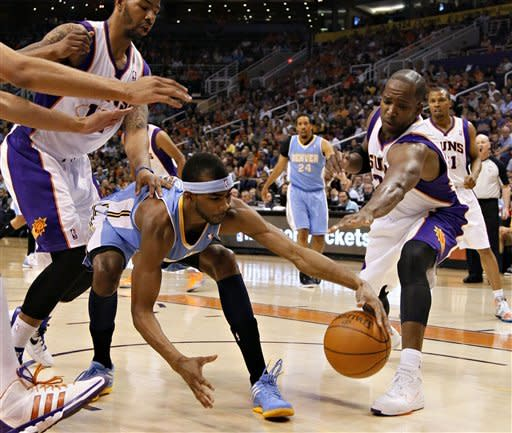 Denver Nuggets' Jordan Hamilton reaches for the ball as Phoenix Suns' Michael Redd, right, and Markieff Morris, left, pursue during the first half of an NBA basketball game on Saturday, April 21, 2012, in Phoenix. (AP Photo/Matt York)