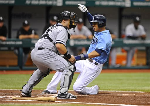 Chicago White Sox catcher Josh Phegley, left, waits for the throw as Tampa Bay Rays' Desmond Jennings scores off Ben Zobrist's sacrifice fly during the first inning of a baseball game on Sunday, July 7, 2013, in St. Petersburg, Fla. (AP Photo/Brian Blanco)