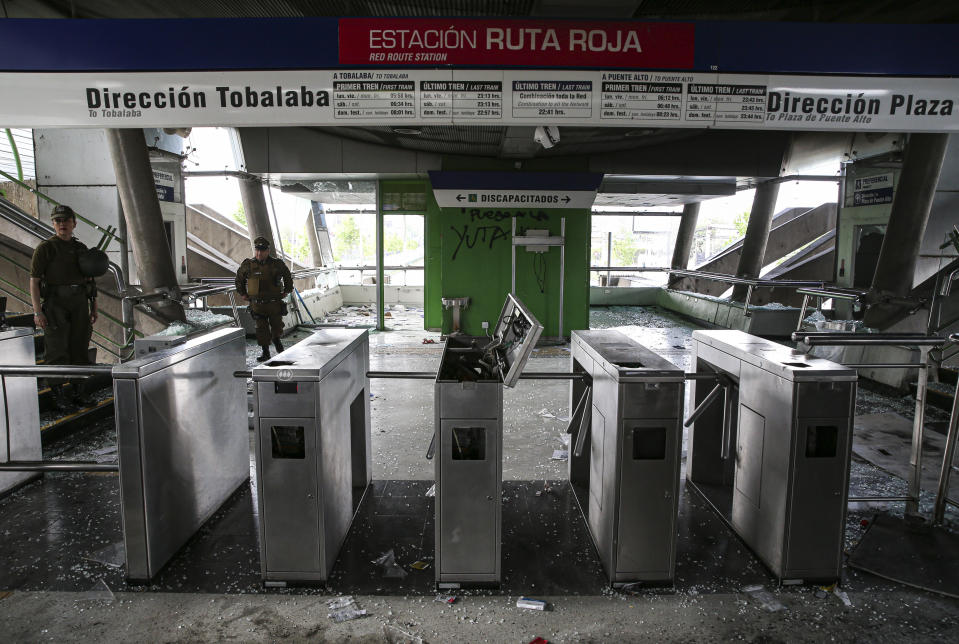 Chilean police stand in a subway station that was damaged during last night's protests, in Santiago, Chile, Saturday, Oct. 19, 2019. The protests started on Friday afternoon when high school students flooded subway stations, jumping turnstiles, dodging fares and vandalizing stations as part of protests against a fare hike, but by nightfall had extended throughout Santiago with students setting up barricades and fires at the entrances to subway stations, forcing President Sebastian Pinera to announce a state of emergency and deploy the armed forces into the streets. (Photo: Esteban Felix/AP)