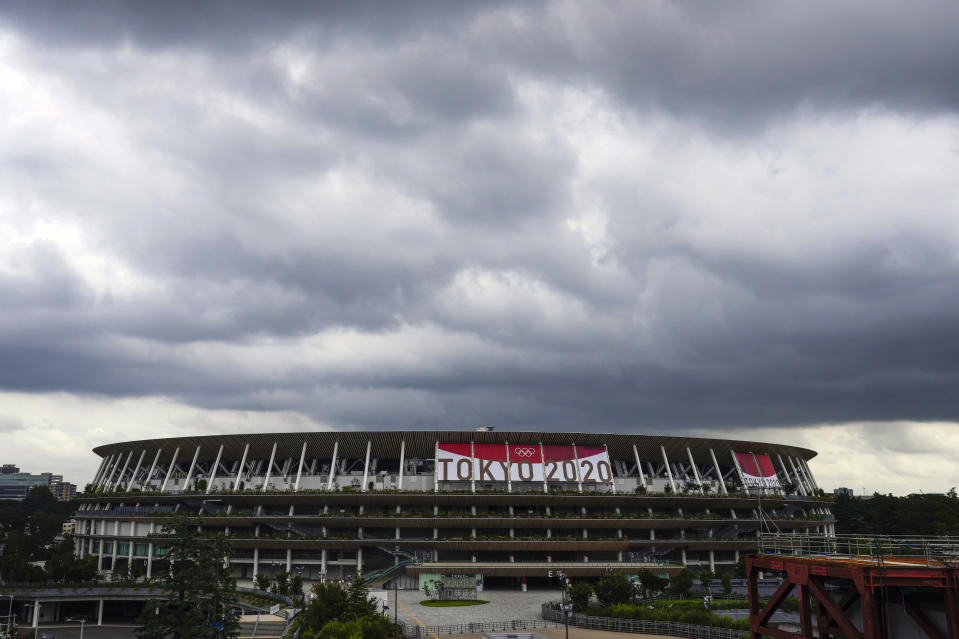 Rain clouds move in over National Stadium Wednesday, June 23, 2021, in Tokyo, one month before the July 23 opening of Tokyo Olympics. The Tokyo Olympics, already delayed by the pandemic, are not looking like much fun: Not for athletes. Not for fans. And not for the Japanese public. They are caught between concerns about the coronavirus at a time when few are vaccinated on one side and politicians who hope to save face by holding the games and the International Olympic Committee with billions of dollars on the line on the other. (AP Photo/Kiichiro Sato)