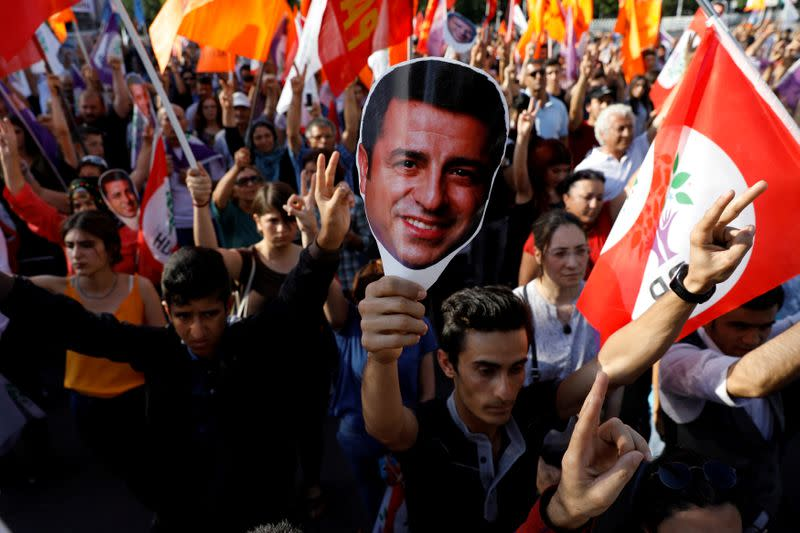 FILE PHOTO: Supporters of Turkey's main pro-Kurdish Peoples' Democratic Party hold masks of their jailed former leader and presidential candidate Selahattin Demirtas during a rally in Ankara