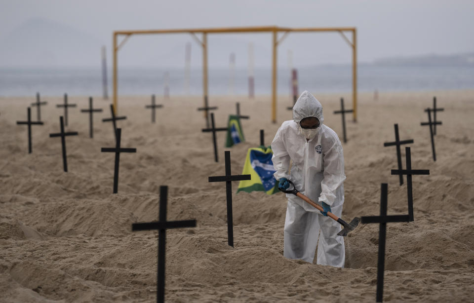 An activist digs symbolic graves on Copacabana beach, in front of a soccer goalpost, during a protest organized by the NGO Rio de Paz against the government's handling of the COVID-19 pandemic in Rio de Janeiro, Brazil, Thursday, June 11, 2020.A Brazilian Supreme Court justice ordered the government of President Jair Bolsonaro to resume publication of full COVID-19 data, including the cumulative death toll, following allegations the government was trying to hide the severity of the pandemic in Latin America's biggest country. (AP Photo/Leo Correa)
