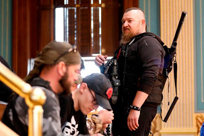 """William Null (R) stands in the gallery of the Michigan Senate Chamber during the American Patriot Rally, organized by Michigan United for Liberty, to demand the reopening of businesses on the steps of the Michigan State Capitol in Lansing, Michigan, on April 30, 2020. Others are unidentified. Thirteen men, including members of two right-wing militias, have been arrested for plotting to kidnap Michigan Governor Gretchen Whitmer and """"instigate a civil war"""", Michigan Attorney General Dana Nessel announced on October 8, 2020. The Nulls were charged for their alleged roles in the plot to kidnap Whitmer, according to the FBI. The brothers are charged with providing support for terroristic acts and felony weapons charges."""