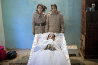 "FILE - In this Tuesday, Nov. 3, 2015 photograph, Maria Ion, a 38 year-old widow, mother of five, who died in last Friday's fire at the Colectiv nightclub where she occasionally worked as a cleaning lady, lies in a coffin wearing a bride dress as two of her children, Denisa, 15 years-old, left, and 11 year-old Alexandra pose next to it, at the family house in Bucharest, Romania. The Oscar-nominated Romanian documentary film ""Collective"" follows a group of journalists delving into the state of health care in the eastern European country in the wake of a deadly 2015 nightclub fire that left dozens of burned victims in need of complex treatment. What they revealed was decades of deep-rooted corruption, a heavily politicized system scarily lacking in care. (AP Photo/Vadim Ghirda, File)"