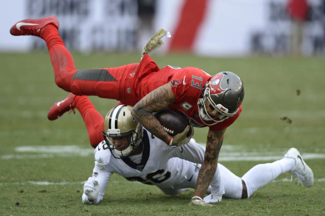 Tampa Bay Buccaneers wide receiver Mike Evans (13) is pended by New Orleans Saints cornerback P.J. Williams (26) during the second half of an NFL football game Sunday, Nov. 17, 2019, in Tampa, Fla. (AP Photo/Jason Behnken)