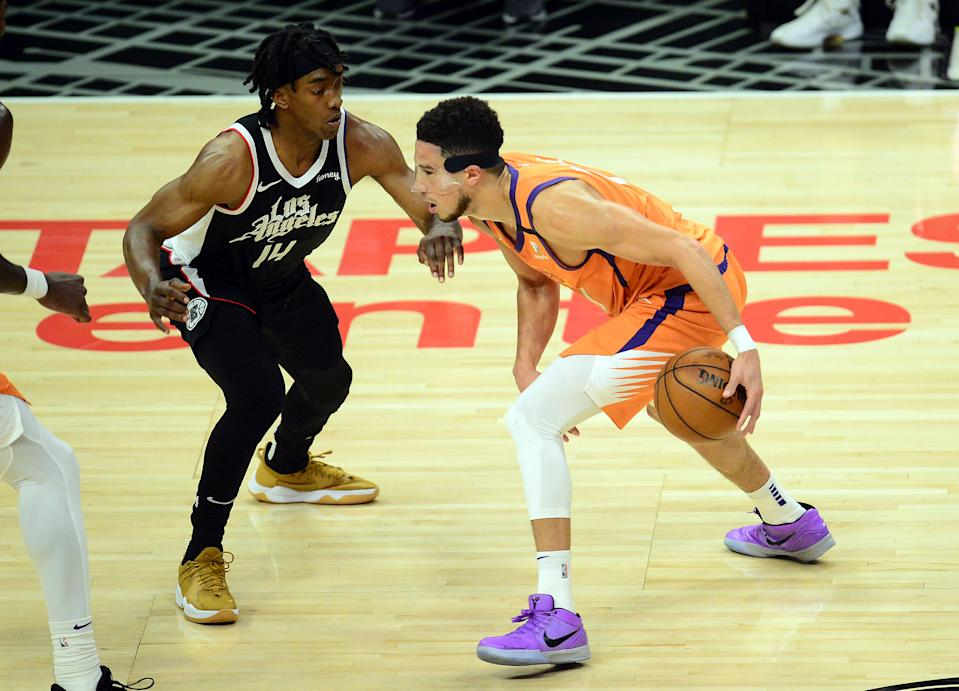 Jun 24, 2021; Los Angeles, California, USA; Phoenix Suns guard Devin Booker (1) moves the ball against Los Angeles Clippers guard Terance Mann (14) during the first half in game three of the Western Conference Finals for the 2021 NBA Playoffs at Staples Center. Mandatory Credit: Gary A. Vasquez-USA TODAY Sports