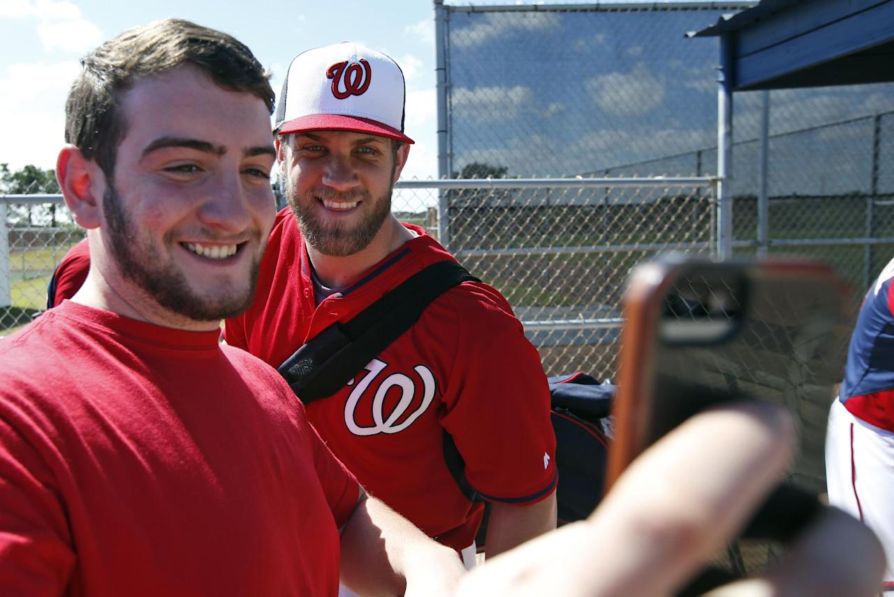 Anthony Cosenza, from Staten Island, N.Y., takes a selfie with Washington Nationals left fielder Bryce Harper after a spring training baseball workout, Thursday, Feb. 20, 2014, in VIera, Fla. (AP Photo/Alex Brandon)