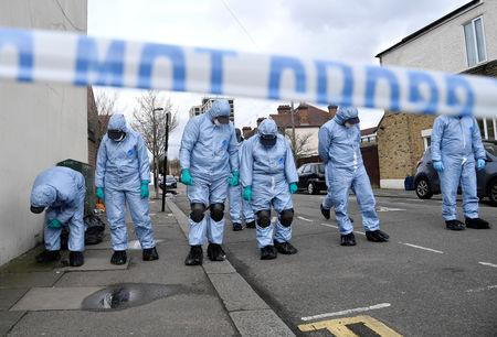FILE PHOTO: Forensic investigators examine the pavement and carriageway on Chalgrove Road, where a teenage girl was murdered, in Tottenham
