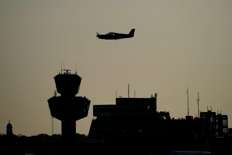 A sports aircraft flies past Tegel Tower, shortly before the last scheduled flight takes off from Berlin's Tegel Airport (TXL) in Berlin, Germany, Sunday, Nov. 8, 2020. With the departure of the Air France aircraft AF 1235 to Paris at 15:00, Tegel Airport will close. (Michael Kappeler/dpa via AP)