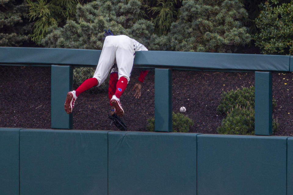 Philadelphia Phillies center fielder Roman Quinn hangs over the wall trying to catch a home run hit by St. Louis Cardinals' Paul DeJong (11) during the third inning of a baseball game, Saturday, April 17, 2021, in Philadelphia. (AP Photo/Laurence Kesterson)