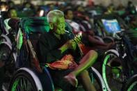 A tricycle driver smokes while attending an outdoor movie screening held by a private organization in Phnom Penh