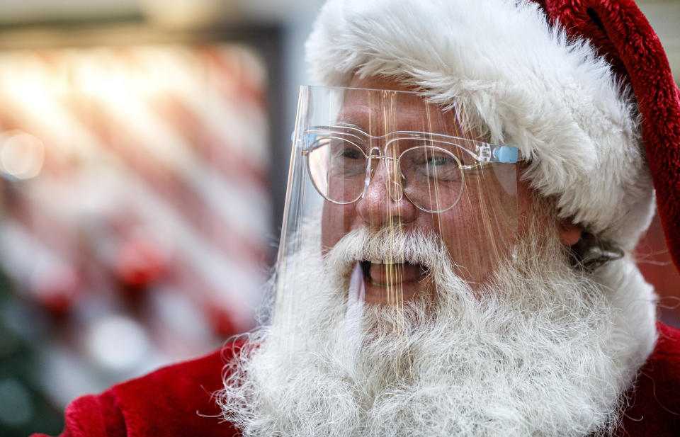 A man dressed as Santa Claus wears a protective face shield at Capital City Mall in Lower Allen Township, Pa., on Wednesday, Nov. 11, 2020. Malls are doing all they can to keep the jolly old man safe from the coronavirus, including banning kids from sitting on his knee, completely changing what a Santa visit looks like. (Dan Gleiter/The Patriot-News via AP)