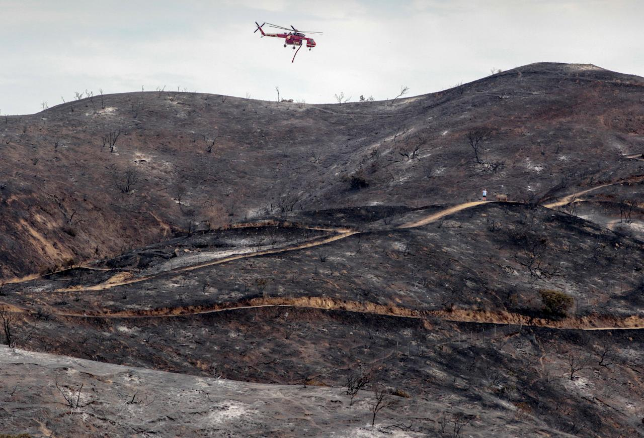 <p>A fire helicopter flies over a charred hillside during the La Tuna Canyon fire over Burbank, Calif., Sept. 3, 2017. (Photo: Kyle Grillot/Reuters) </p>