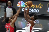 Miami Heat forward Jimmy Butler, right, shoots over Chicago Bulls center Wendell Carter Jr., during the first half of an NBA basketball game in Chicago, Friday, March 12, 2021. (AP Photo/Nam Y. Huh)