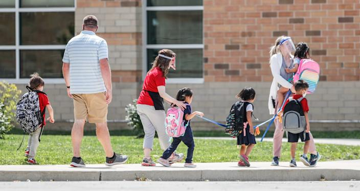 Students line up to get on the bus and head home after the first day of classes at Homecroft Elementary School in Indianapolis Wednesday.