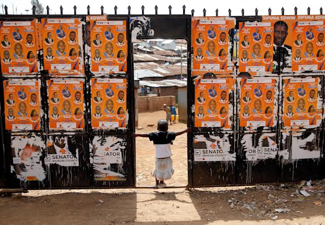<p>A child plays at the entrance of a polling station pasted with campaign posters in Sarang'ombe ward ahead of the Presidential election at the Kisumu Ndogo village in Kibera slums of Nairobi, Kenya, Aug. 6, 2017. (Photo: Thomas Mukoya/Reuters) </p>