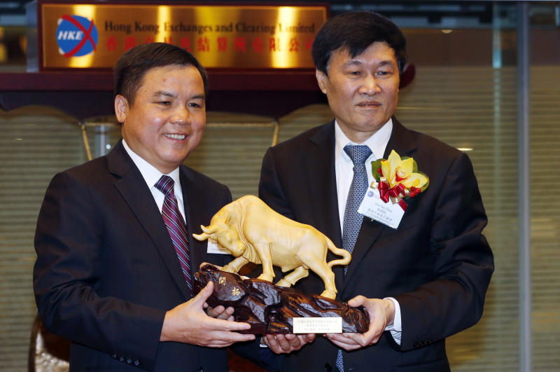 China Cinda Asset Management Chairman Hou Jianhang, right, presents a gift to the Listing Committee Member Liu Ting An during the company listing ceremony at the Hong Kong Stock Exchange, Thursday, Dec. 12, 2013. A Chinese bad-debt management company's shares are soaring in their Hong Kong debut, highlighting strong investor appetite for a business that will flourish if the world's No. 2 economy stumbles. China Cinda Asset Management Co.'s shares jumped as much as 23 percent after they started trading Thursday. (AP Photo/Kin Cheung)