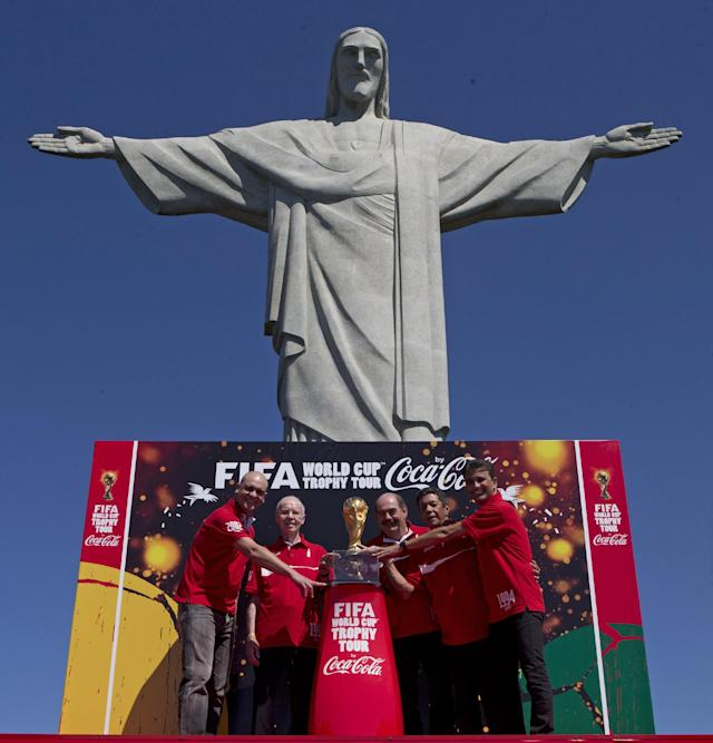 Brazil's former World Cup champion soccer players, from left, Marcos, Zagallo, Rivellino, Amarildo and Bebeto pose for a photo with the FIFA World Cup trophy in front the Christ the Redeemer statue at the opening ceremony of the FIFA WCUP Trophy Tour in Rio de Janeiro, Brazil, Thursday, Sept. 12, 2013. The trophy is set to embark on an extensive journey, covering over 80 countries, giving the opportunity to millions of fans to enjoy the authentic solid-gold trophy. (AP Photo/Silvia Izquierdo)