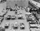 """In this 1918 photo made available by the Library of Congress, volunteer nurses from the American Red Cross tend to influenza patients in the Oakland Municipal Auditorium, used as a temporary hospital. (Edward A. """"Doc"""" Rogers/Library of Congress via AP)"""