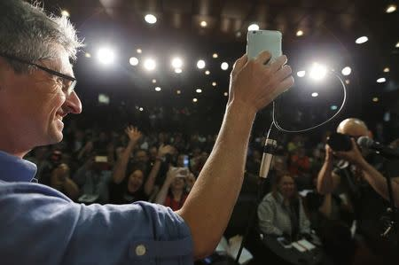 """71st Cannes Film Festival - News conference for film """"The Picture Book"""" (Le livre d'image) in competition - Cannes, France May 12, 2018. Producer Fabrice Aragno holds his mobile phone for a video conference with director Jean-Luc Godard as he speaks about his film. REUTERS/Regis Duvignau"""