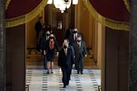 The House Sergeant of Arms (front) walks with House impeachment managers to the Senate floor as they arrive for the start of the trial of former US president Donald Trump