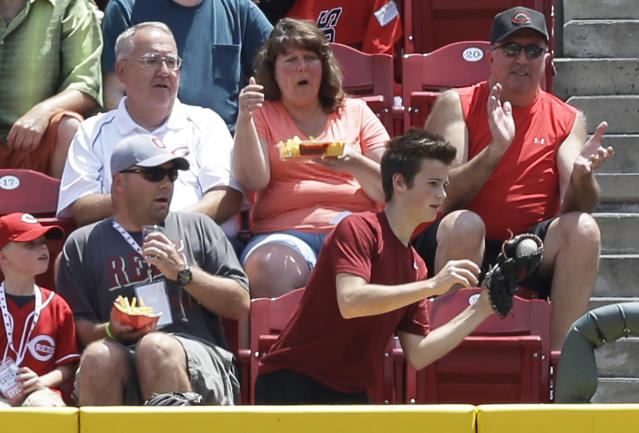 A young fan catches a two-run home run hit by Cincinnati Reds' Todd Frazier off Toronto Blue Jays starting pitcher R.A. Dickey in the fifth inning of a baseball game, Sunday, June 22, 2014, in Cincinnati. (AP Photo/Al Behrman)