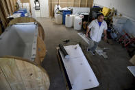In this Wednesday, Aug. 11, 2021, photo, Chris Olachia walks past a nearly completed human body composting vessel in Arvada, Colo. On Sept. 7, Colorado became the second state after Washington to allow human body composting, and Oregon will allow the practice beginning next July. The vessel will be packed with wood chips and straw and will be able to compost a body in six months. About the size of a standard grave, the rectangular insulated wooden box is lined with waterproof roofing material and packed with wood chips and straw. Two large spool wheels on either end allow it to be rolled across the floor, providing the oxygenation, agitation and absorption required for a body to compost. (AP Photo/Thomas Peipert)