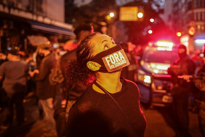 "RIO DE JANEIRO, BRAZIL - JUNE 28: A demonstrator wearing a face mask that reads in Portuguese ""Go Away Bolsonaro"" during a rally against President Jair Bolsonaro and governor of Rio de Janeiro Wilson Witzel amidst the coronavirus (COVID-19) pandemic at Copacabana beach on June 28, 2020 in Rio de Janeiro, Brazil. The protest was organized by left-wing parties and social movements. (Photo by Andre Coelho/Getty Images)"