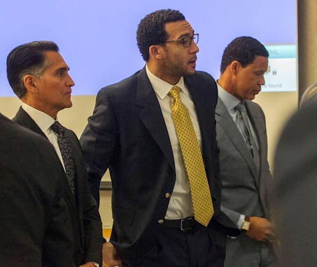 Former NFL football player Kellen Winslow Jr., center, stands as the jury enters the courtroom during his rape trial. Winslow's attorneys Brian Watkins, right, and Marc Carlo, left, flank him. (AP)