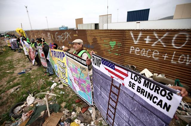 "People hold signs during a protest while standing in front of the current border fence and near the prototypes of U.S. President Donald Trump's border wall, in Tijuana, Mexico March 13, 2018. The sign on the right reads ""Trump, walls can be jumped over"". (Photo: Edgard Garrido/Reuters)"